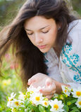 Young woman smelling flowers. Royalty Free Stock Images