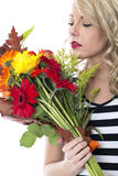 Young Woman Smelling and Holding a Bunch of Flowers Royalty Free Stock Photos