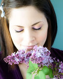 Young woman smelling lilacs Stock Image