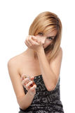Young woman smelling perfume on her wrist Royalty Free Stock Images