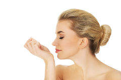 Young woman smelling perfume on her wrist. Stock Image