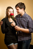 Young woman smelling red rose presented by young man Stock Photos