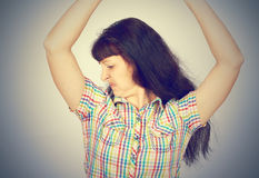 Young woman, smelling, sniffing her armpit Royalty Free Stock Image