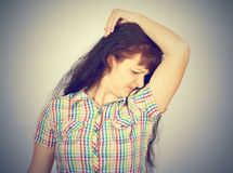 Young woman, smelling, sniffing her armpit Royalty Free Stock Photo