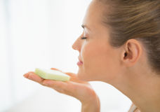 Young woman smelling soap bar. In bathroom stock images