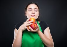 Young woman smelling some fresh and sweet nectarines. In the market Royalty Free Stock Photos