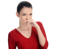 Young woman smelling something bad. Dissgusting odor. Girl squinting and holding her hand at her nose. Isolated on white background Stock Photography
