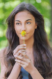 Young woman smelling yellow flower Stock Images
