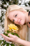 Young Woman Smelling Yellow Rose Stock Photography