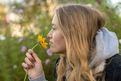 A young woman smells at a flower stock photos