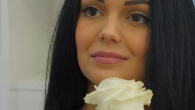 Young woman smells white rose and smiles Stock Photo