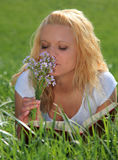 Young woman smells at wild flowers Stock Photography