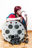 Young woman smile behind big movie cinema reel biting filmstrip Stock Photo