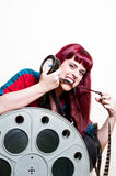 Young woman smile behind big movie cinema reel biting filmstrip Royalty Free Stock Photography