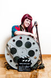 Young woman smile behind big movie cinema reel and clapper Royalty Free Stock Images