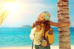 Young woman smile standing with backpack on coast sea and looki Stock Photography