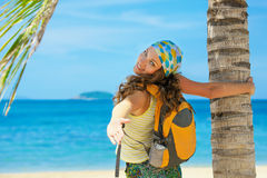 Young woman smile standing with backpack on coast sea and looki Stock Photos