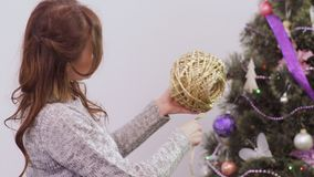 Young woman with a golden thread near Christmas tree stock video