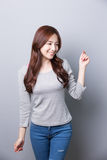 Young woman smile to you. She dressed in winter clothing jeans with isolated gray background, asian Stock Images