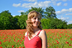 The young woman smiles in a poppy field Royalty Free Stock Images
