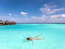 Young woman smiles, swiming in ocean, Maldives. Landscape in a sunny day Stock Image