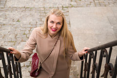 Young woman  smiles and walks up the stairs Royalty Free Stock Image