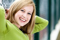 Young woman smiling. Teenage girl leaning against a chain-link fence Royalty Free Stock Images