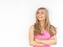 Young woman smiling with arms crossed and looking up Royalty Free Stock Photos