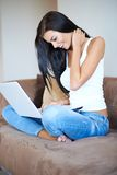 Young woman smiling as she browses on a laptop Stock Photography