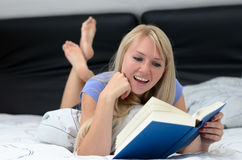 Young woman smiling as she reads a book Stock Photos