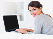 Young woman smiling in bed with a laptop Royalty Free Stock Photos