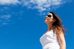 Young Woman Smiling with a Blue Sky Background Stock Photo