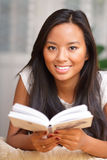 Young woman smiling with a book Royalty Free Stock Images