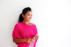 Young woman smiling with a bottle of water against a white wall Stock Photos