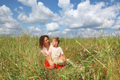 Young woman and smiling boy sitting on meadow Royalty Free Stock Photography