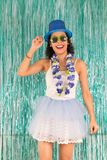 Young woman is smiling. Brazilian is costumed for the party of C. Smiling woman with hand on brim of hat. Happy Brazilian is costumed for the Carnival party Royalty Free Stock Photo