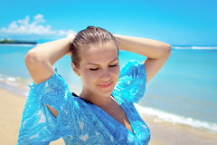 Young woman smiling at camera in front of sea Stock Photos