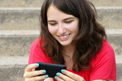 Young woman smiling at cell phone. Young woman, teenager girl or student reading text on her cell phone and smiling, perfect for social media, networking or Stock Photo