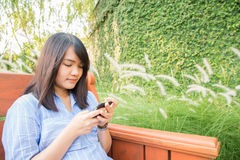 Young woman smiling and cell phone texting sitting on a park bench in autumn or fall. Stock Image