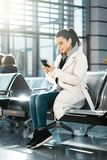 Young woman smiling and chatting by mobile phone in airport before flight. Young beautiful woman smiling, looking at mobile phone and chatting. Modern light royalty free stock photography