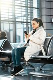 Young woman smiling and chatting by mobile phone in airport before flight. Young beautiful woman smiling, looking at mobile phone and chatting. Modern light stock photo