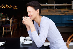 Young woman smiling with coffee at cafe Royalty Free Stock Images