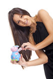 Young woman smiling with a cow piggy bank Stock Photo