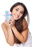 Young woman smiling with a cow piggy bank Royalty Free Stock Photography