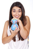 Young woman smiling with a cow piggy bank Royalty Free Stock Photos