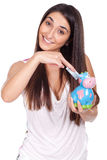 young woman smiling with a cow piggy bank Stock Image