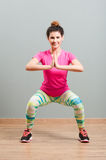 Young woman smiling and doing squats in the gym Royalty Free Stock Photo