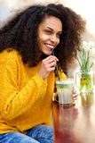 Young woman smiling with drink at cafe Stock Photo