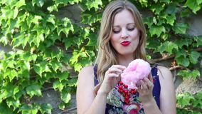 Young Woman Smiling and Eating Pink Cotton Candy With Ivy Background stock footage