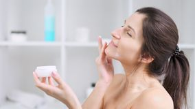 Young woman smiling and enjoying applying anti-ageing moisturizing cream on perfect skin face. Attractive young woman smiling and enjoying applying anti-ageing stock video footage